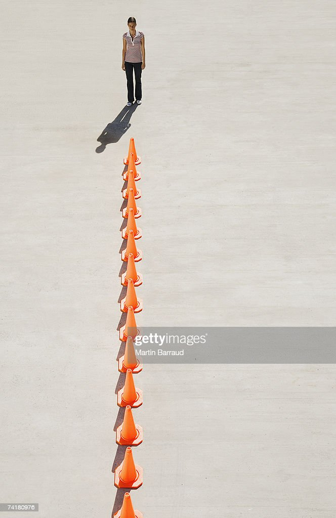 Woman looking at row of traffic cones : Stock Photo