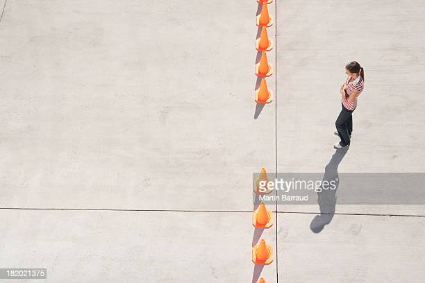 Woman looking at row of traffic cones with gap