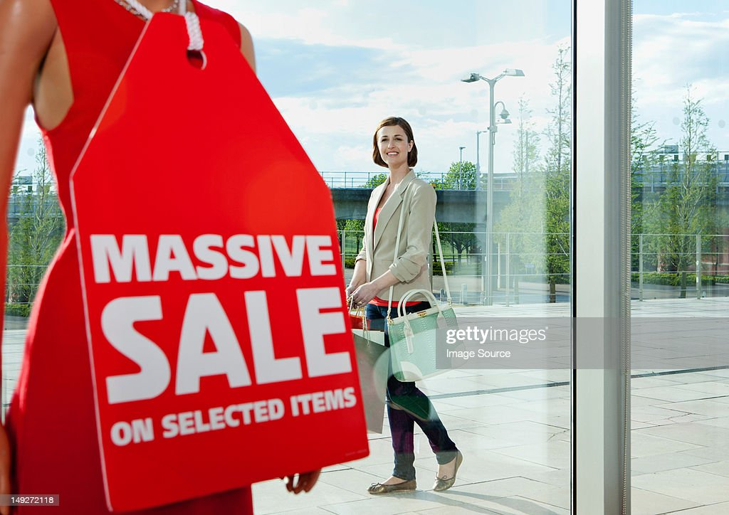 Woman looking at sale sign in shop window
