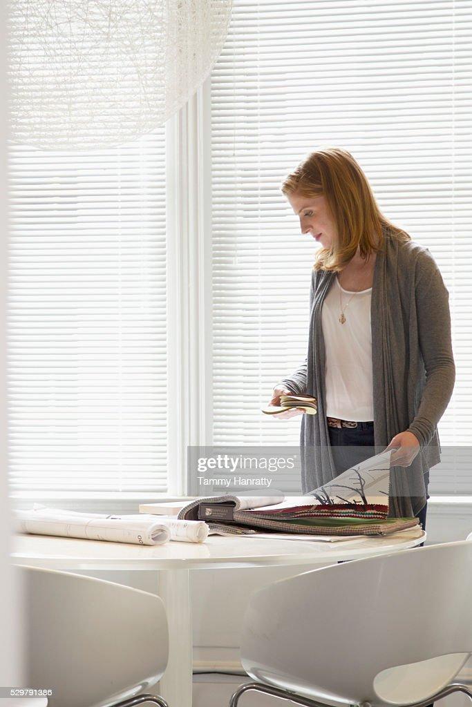 Woman looking at samples of wallpaper : Foto de stock