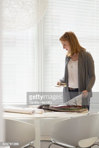 Woman looking at samples of wallpaper : Stock Photo