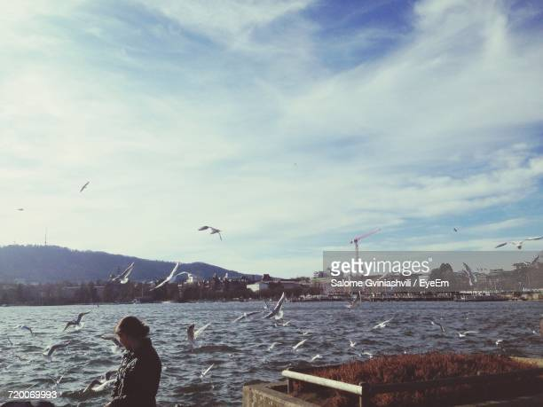 Woman Looking At Seagulls Flying Over River By City Against Cloudy Sky