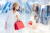 woman holding a smartphone,looking at shop window display,she was attracted by the beautiful clothing in shop.