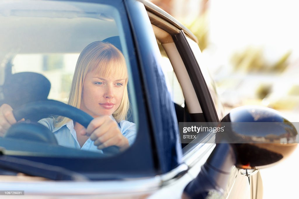 Woman looking at side view mirror while driving a car : Stock Photo