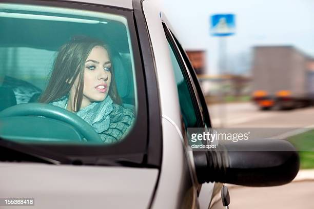 Woman looking at side view mirror while driving a car