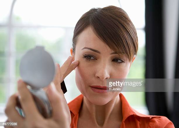 Woman looking at skin in a mirror.