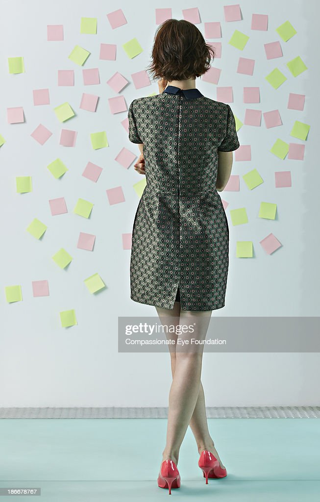 Woman looking at sticky notes on board : Stock Photo