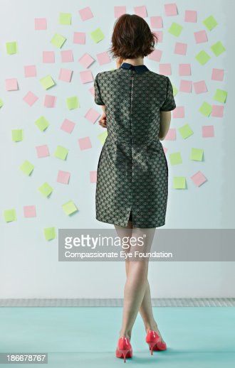 Woman looking at sticky notes on board