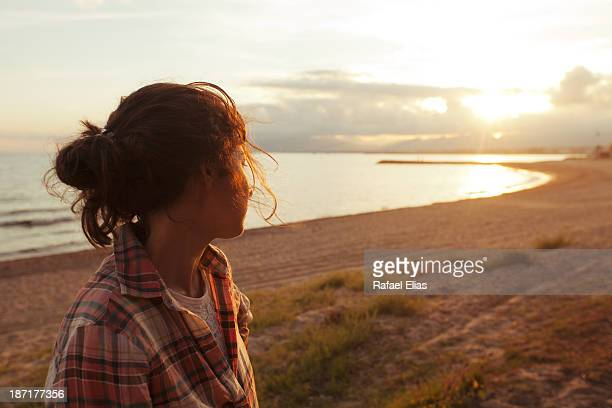Woman looking at sunrise on the beach