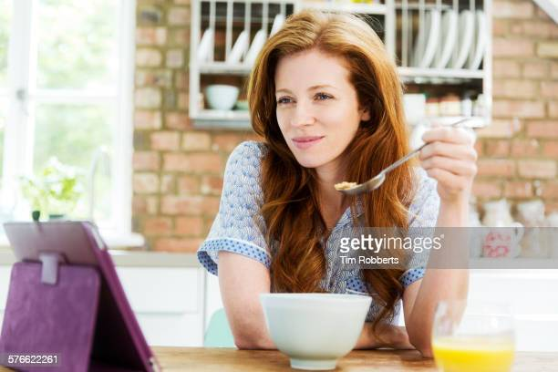 Woman looking at tablet at breakfast