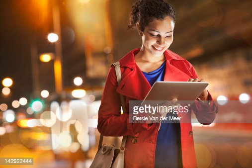 Woman looking at ipad standing in city at night. : Stock Photo