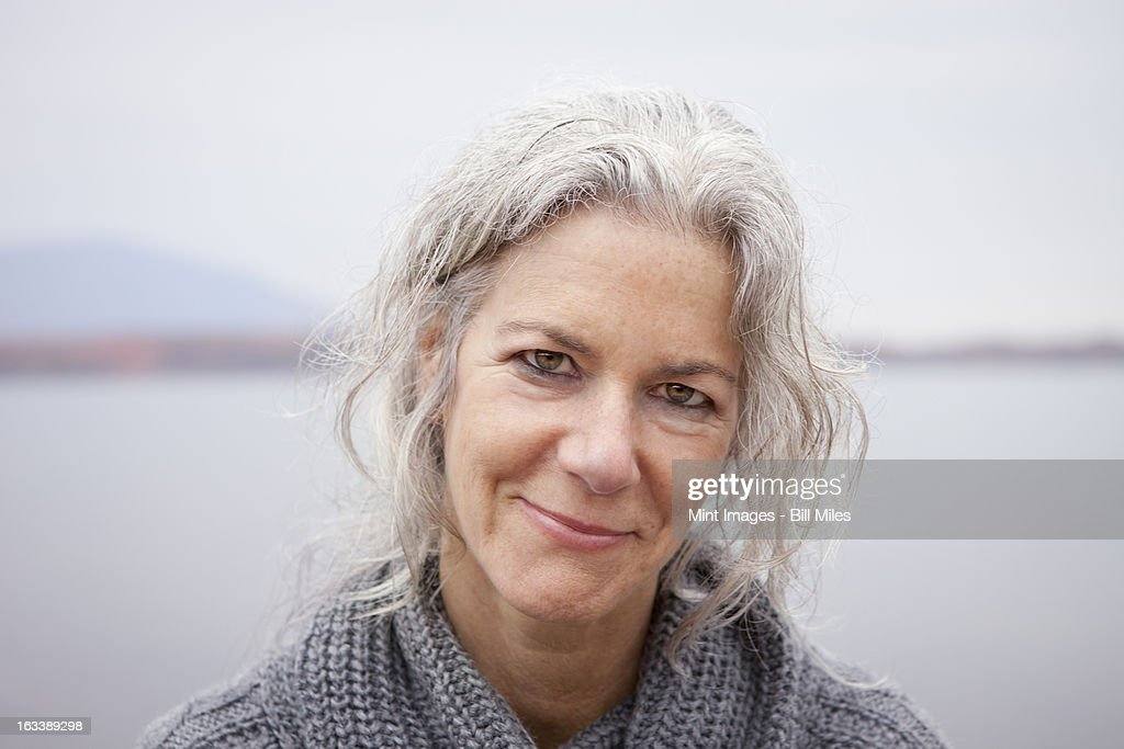 A woman looking at the camera, by the shore of a lake.  : Stock Photo
