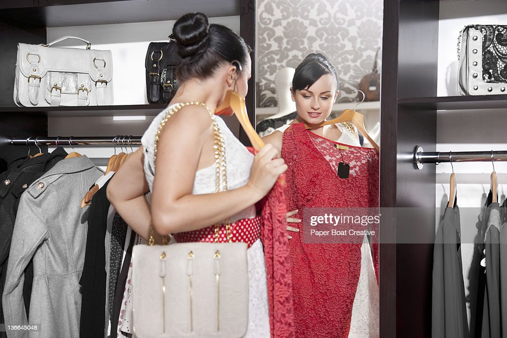 woman looking at the mirror holding a red dress