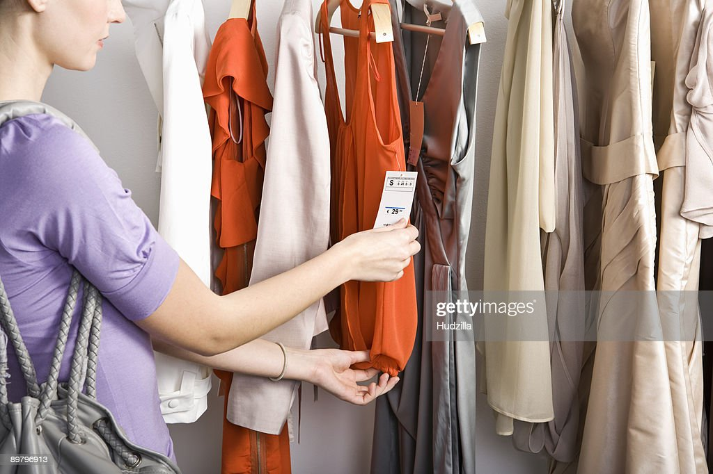A woman looking at the price tag of a top on a clothing rail