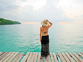 Woman looking at the sea on wooden jetty