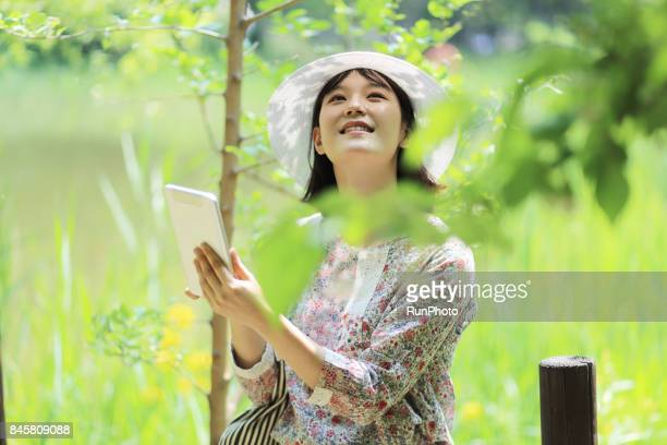 woman looking at the sky by operating a table laptop