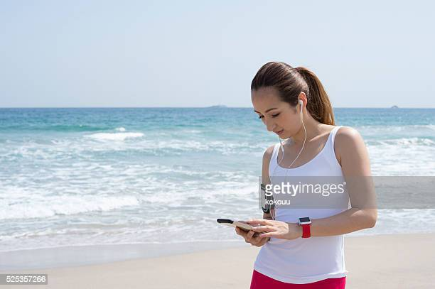 Woman looking at the smartphone at the seaside