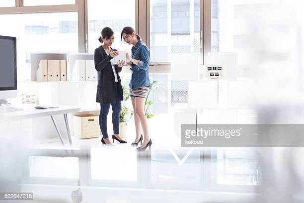 女性のタブレットを見ているのは、スタイリッシュなオフィス