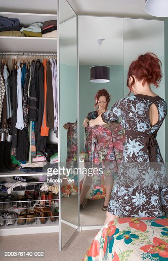 Woman looking at top in bedroom, rear view : Stock Photo