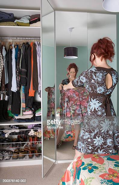 Woman looking at top in bedroom, rear view