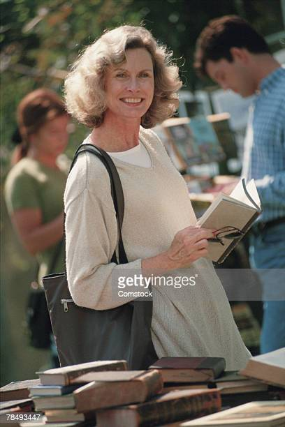 Woman looking at used books at yard sale