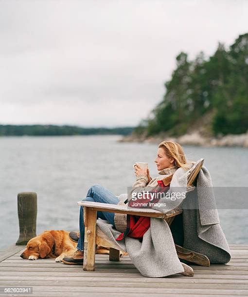Woman looking at water with hot drink
