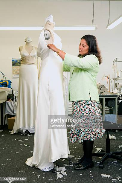 Woman looking at wedding dress on form