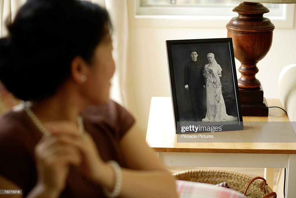 Woman looking at wedding photograph in living room, focus on photograph : Stock Photo