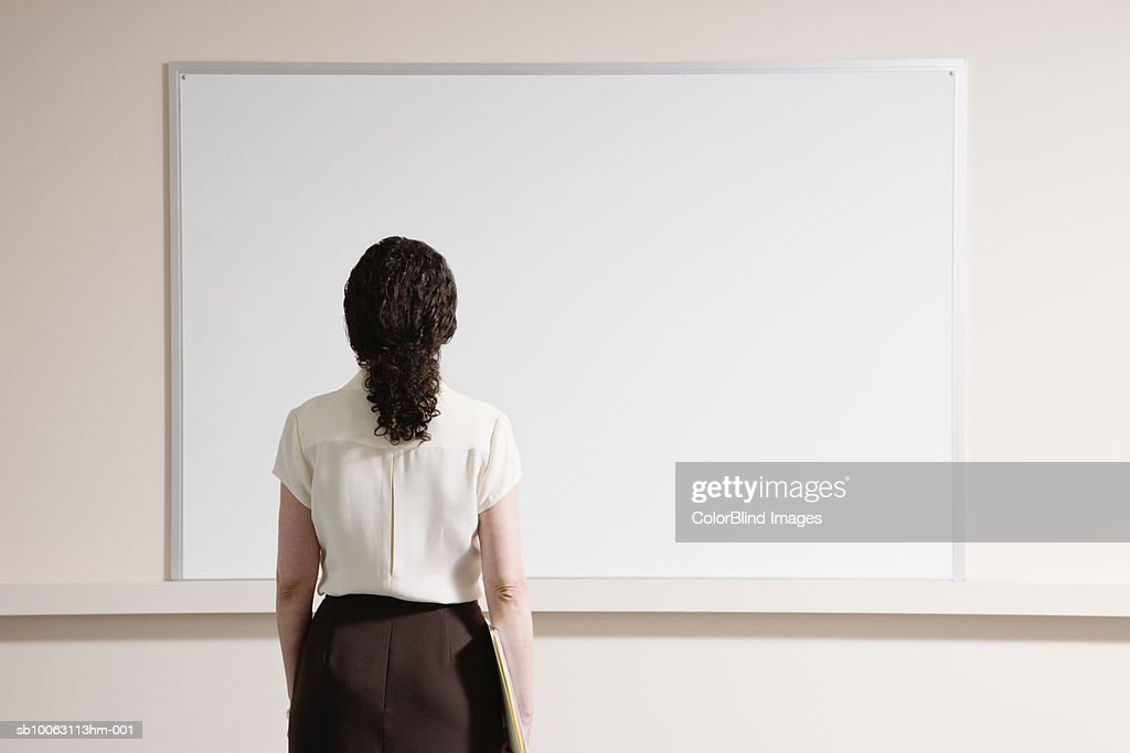 Woman looking at whiteboard, rear view : Stock Photo