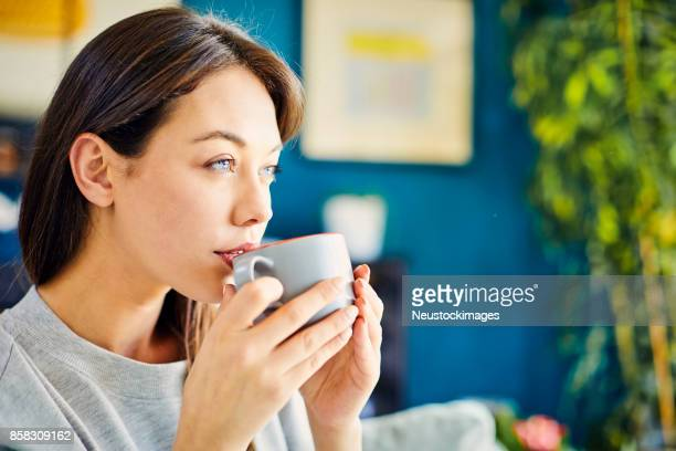 Woman looking away while drinking coffee at home