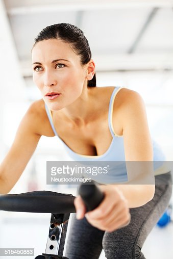 Woman Looking Away While Spinning On Exercise Bike In Club