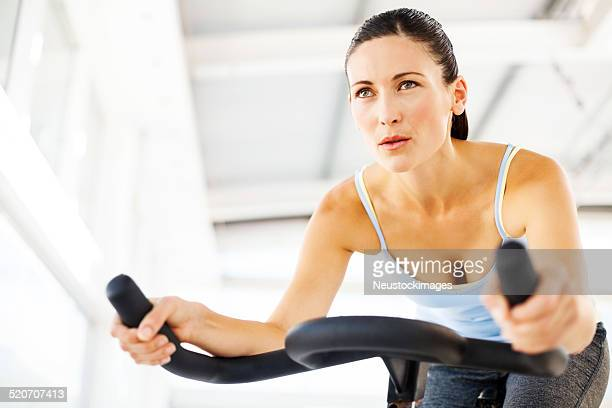 Woman Looking Away While Training On Exercise Bike In Gym