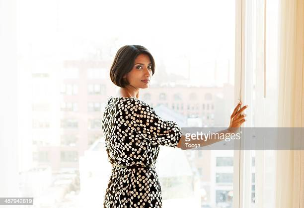 Woman looking back at camera in front of window
