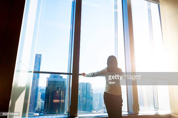 Woman looking cityscape through the window