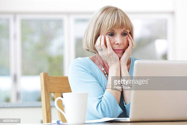 Woman looking concerned at laptop
