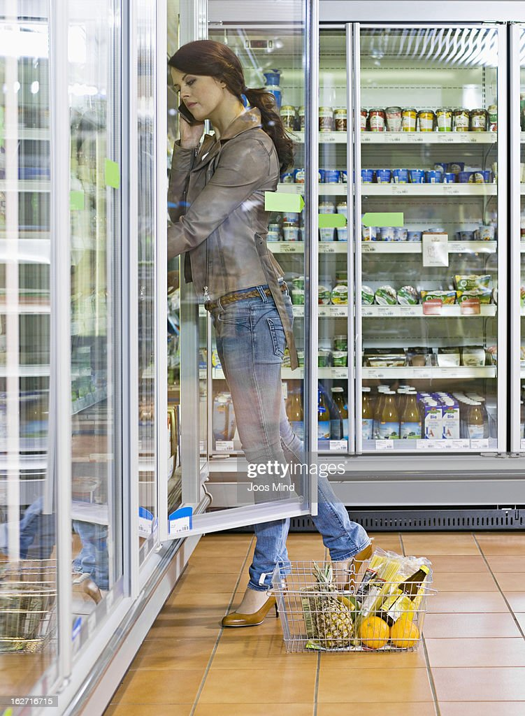 woman looking diary produce in supermarket : Stock Photo