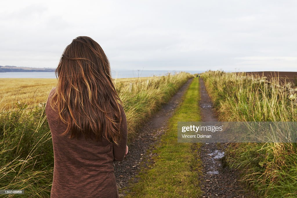 Woman looking down a country lane : Stock Photo