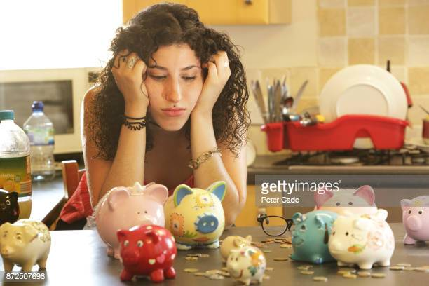 Woman looking fed up looking at piggy banks and change