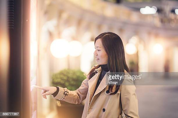 Woman looking for directions with a digital kiosk