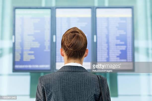 女性を探している空港での航空便の情報