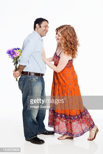 Woman looking for flowers behind man's back against white background : Stock Photo