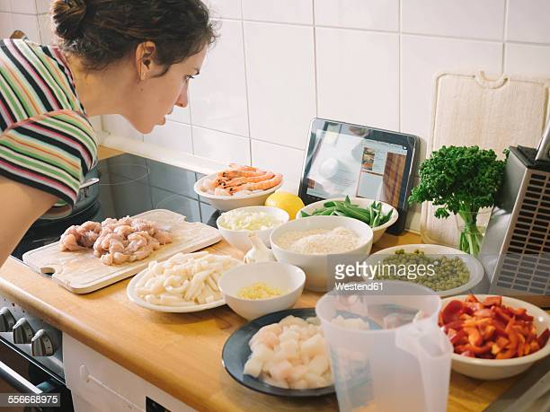 Woman looking for pealla recipe on internet with ingredients in kitchen