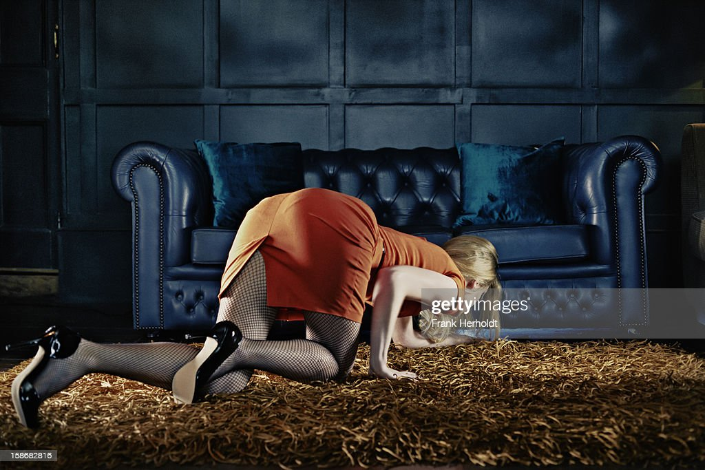 Woman looking for phone under sofa : Stockfoto