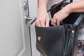 Woman looking for something such as keys in her handbag in front of her apartment