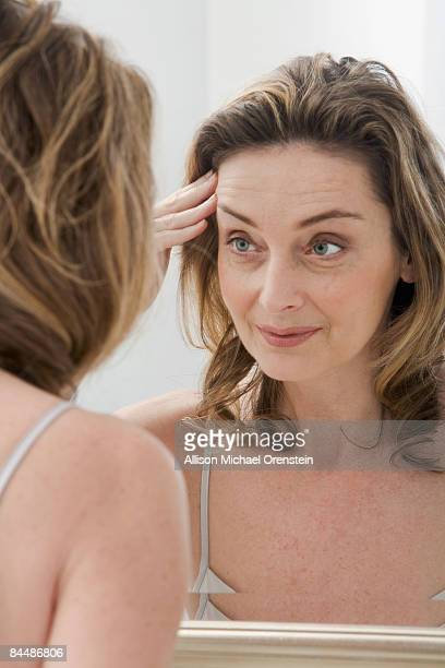 Woman looking for wrinkles in mirror