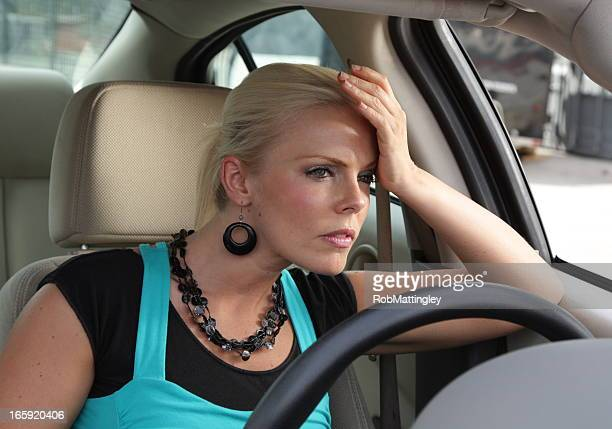 Woman looking frustrated while sitting in a car