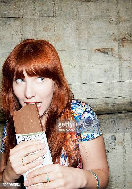 woman looking guilty eating chocolate bar
