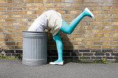 Woman looking in a dustbin