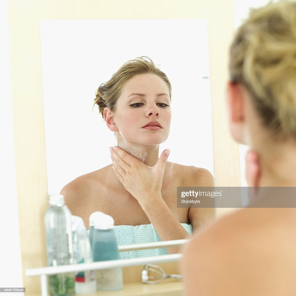 woman looking in a mirror and applying lotion on her neck : Stock Photo