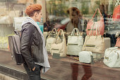 Beautiful young woman looking in a shop window with handbags on the street